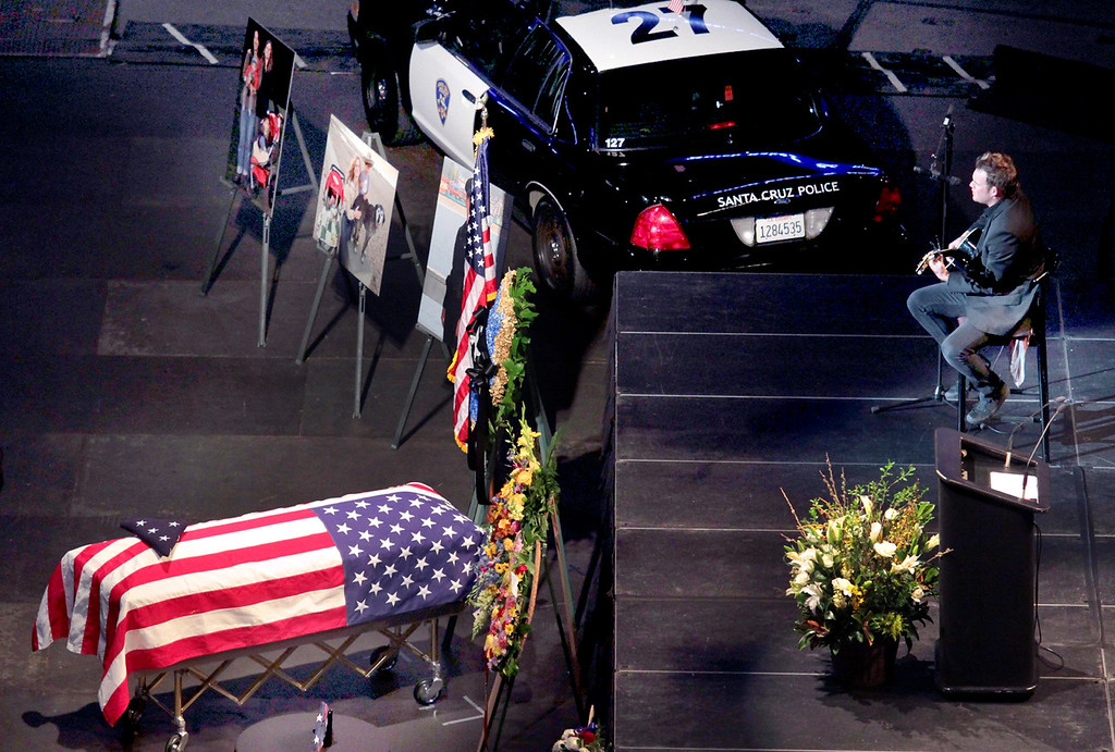 . A Santa Cruz Police cruiser is parked next to the casket of detective Elizabeth Butler as James Durbin sings during Thursday\'s memorial service. (Shmuel Thaler/Sentinel)