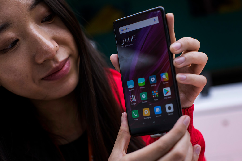 . A woman shows the new Xiaomi Mi MIX 2 during the Mobile World Congress wireless show, in Barcelona, Spain, Monday, Feb 26, 2018. The annual Mobile World Congress (MWC) runs from 26 February - 1 March and draws over 2,300 exhibitors to Barcelona, including industry heavyweights Samsung, Huawei and Nokia. (AP Photo/Emilio Morenatti)