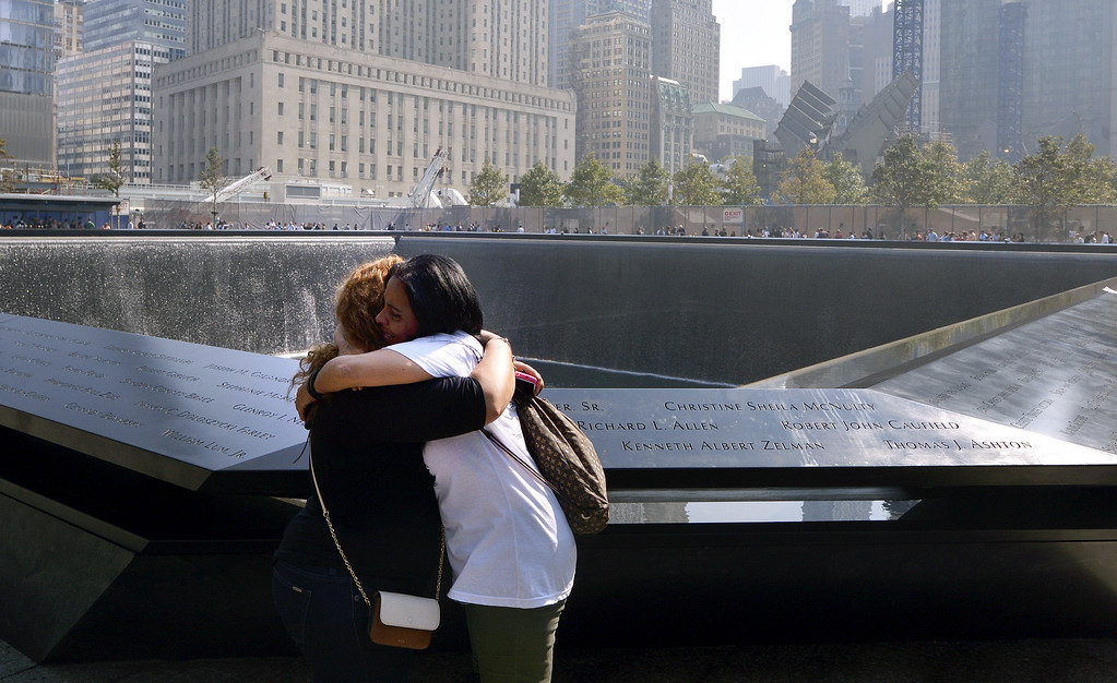 . Grissel Valentin (L) and Eileen Esquilin, who both lost family members and are both from New York, embrace at the edge of the North Pool at the 9/11 Memorial during ceremonies for the twelfth anniversary of the terrorist attacks on lower Manhattan at the World Trade Center site on September 11, 2013 in New York City. (Photo by Justin Lane-Pool/Getty Images)