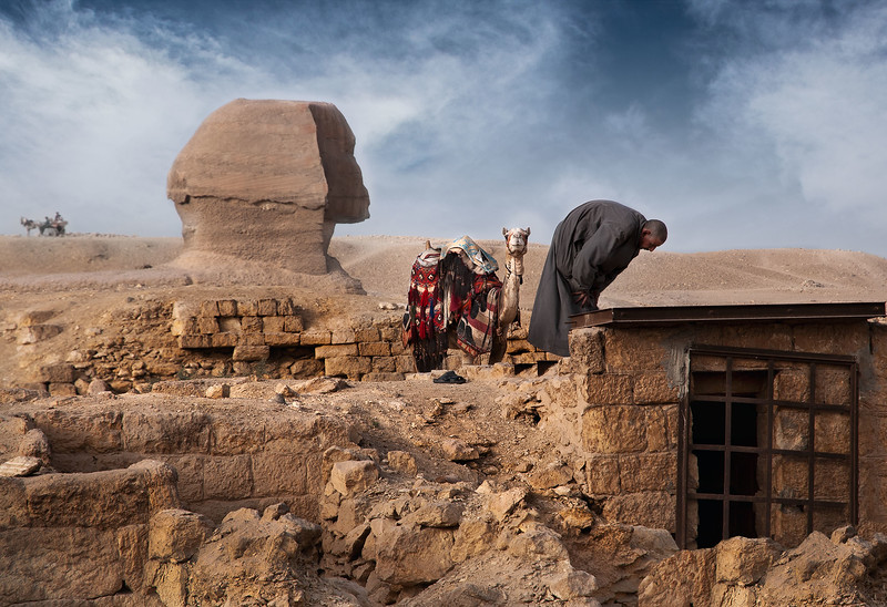 A camel guide interrupts his work in order to pray on the ancient tombs. The Sphinx towers in the background.   Giza, Cairo, Egypt, 2010.