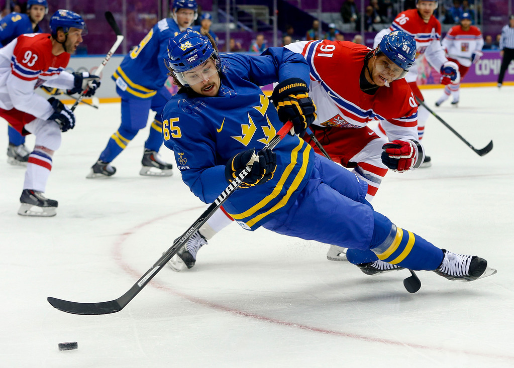 . Sweden defenseman Erik Karlsson (65) loses his footing as he passes the puck from Czech Republic forward Martin Erat in the first period of a men\'s ice hockey game at the 2014 Winter Olympics, Wednesday, Feb. 12, 2014, in Sochi, Russia. (AP Photo/Mark Humphrey)