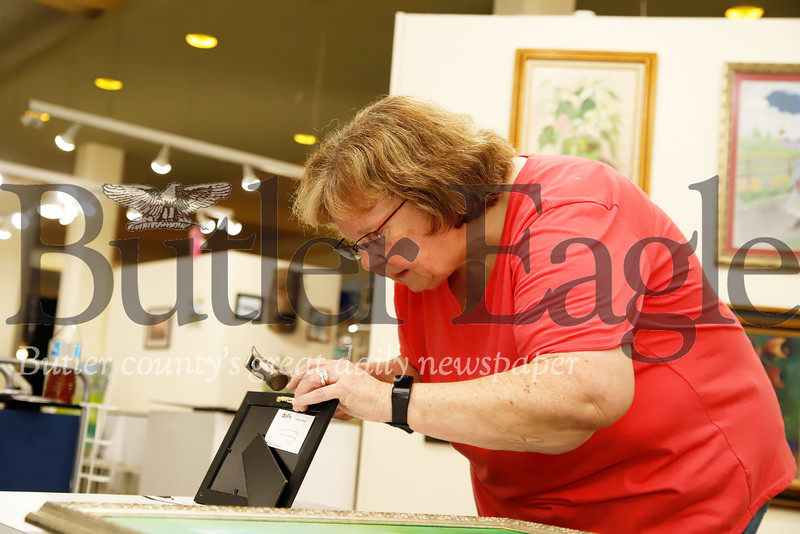 Butler Arts Center volunteer Shirley McCauley of Slippery Rock adjusts the hanger on the back of a frame before hanging it at the Center's Maint Street gallery. Volunteers and gallery staff spent the evening preparing for the gallery's latest exhibit set to open Friday and feature a number of local artists.  Seb Foltz/Butler Eagle