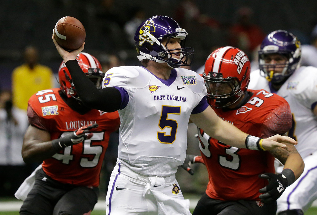 . East Carolina quarterback Shane Carden (5) looks for a receiver as he is pursued by Louisiana-Lafayette defensive end Emeka Onyenekwu (45) and defensive lineman Cordian Hagans (93) in the first half of the New Orleans Bowl, an NCAA college football game in New Orleans, Saturday, Dec. 22, 2012. (AP Photo/Bill Haber)