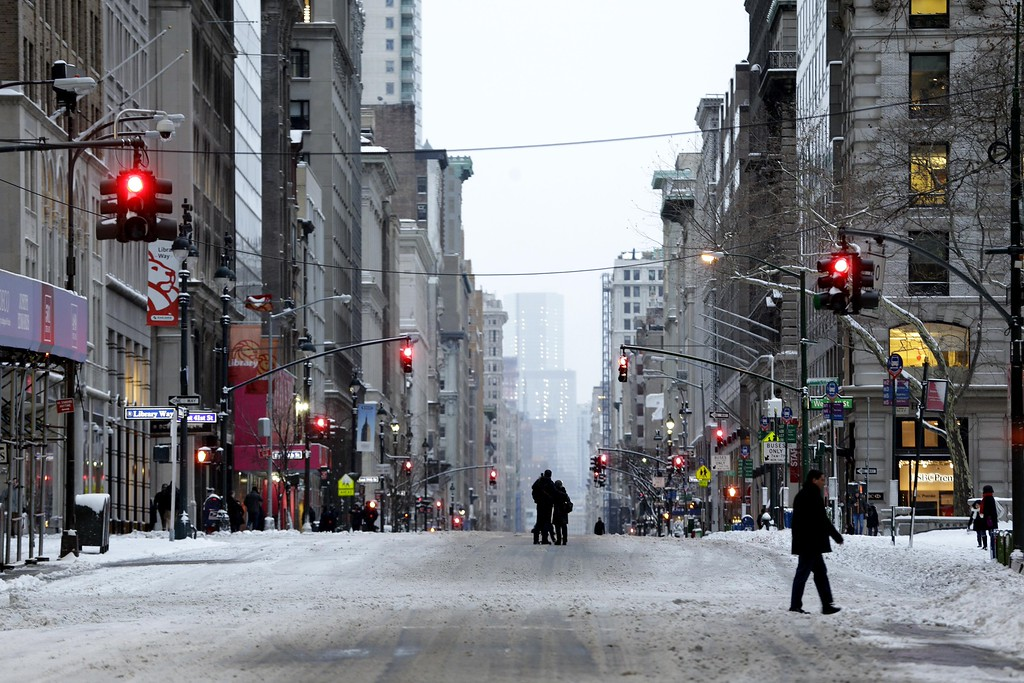 . People walk in the middle of a car-free Fifth Avenue in New York, Tuesday, Jan. 27, 2015. A storm packing blizzard conditions spun up the East Coast early Tuesday, pounding parts of coastal New Jersey northward through Maine with high winds and heavy snow. (AP Photo/Seth Wenig)