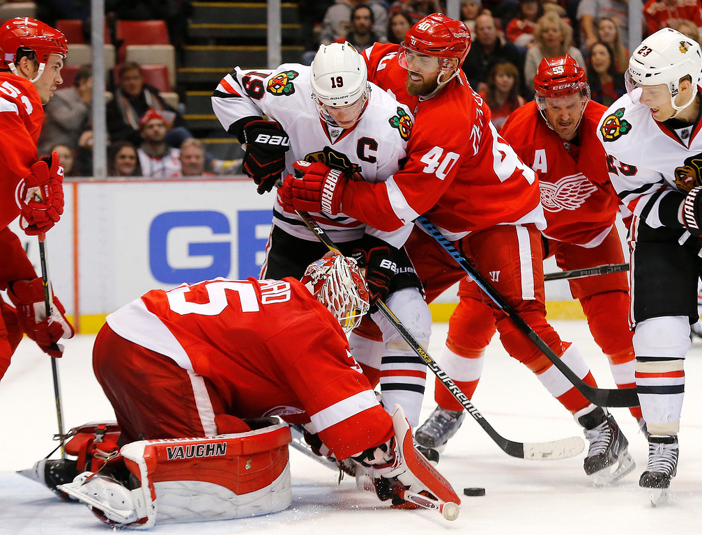 . Detroit Red Wings left wing Henrik Zetterberg (40) wraps Chicago Blackhawks center Jonathan Toews (19) up as goalie Jimmy Howard (35) stops a shot in the third period of an NHL hockey game in Detroit, Friday, Nov. 14, 2014. Detroit won 4-1. (AP Photo/Paul Sancya)