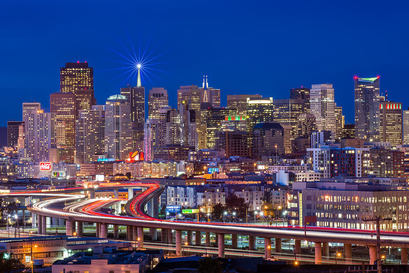 "One of the classic holiday shots that every SF photographer should have is the Potrero Hill cityscape. The beautiful S-curve of highway 280 draws the eye right into the city and certain buildings are lit up with beautiful holiday colors. The star on top of the Transamerica Building tops it all off.   Zack had just received his brand new D600 and wanted to give it a try. We drove on over and arrived early at the corner of 19th St. and Texas Ave (thus where part of the name ""Lone Star City"" comes from). We were the first photographers to arrive but I knew that wouldn't last long. In all there were 4 other photographers that joined us. For almost the whole time we were able to stand in the middle of the road and direct cars around us. It was pretty fun watching the cars weave in and out of photographers. So nice of them!   I wanted to choose a composition that included as much of the holiday lights as I could, without showing *too* many buildings and making everything small. I also didn't want to put the S-curve too close to the edge of the photo. Thanks to a number of other photographers who have shot this in the past I knew that Caltrain often crossed under the highway and every time a train passed by I would frantically click away, adding the trains light trails to the photo. I also got lucky when 1 car and a truck decided to change lanes on the highway, providing beautiful blinking lights on the S-curve!   Happy holidays!  Nikon D800 w/Nikkor 80-200mm f/2.8D ED AF: 112mm, f/13, 30 sec, ISO 100 Star shot at f/16 No Filters, No HDR"