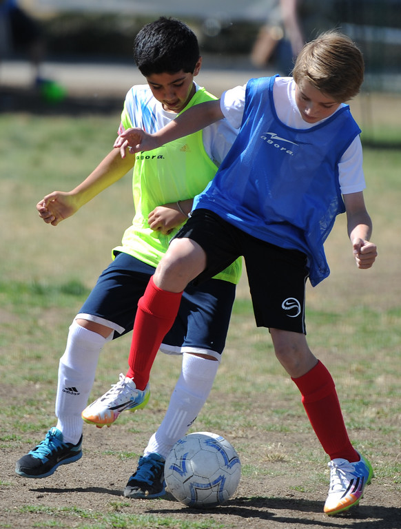 ". Dariush Dahesh and Evan Pritchard battle for control of the ball. In honor of the AYSO\'s 50th anniversary as the nation�s most active and open youth soccer organization, kids at Balboa Park in Encino will join efforts around the country Saturday--over 500,000 players,125,000 volunteers,100 community-based events and a national soccer festival--to set a world record for the ""largest pickup game on Earth.\"" Encino, CA. 5/3/2014(Photo by John McCoy / Los Angeles Daily News)"