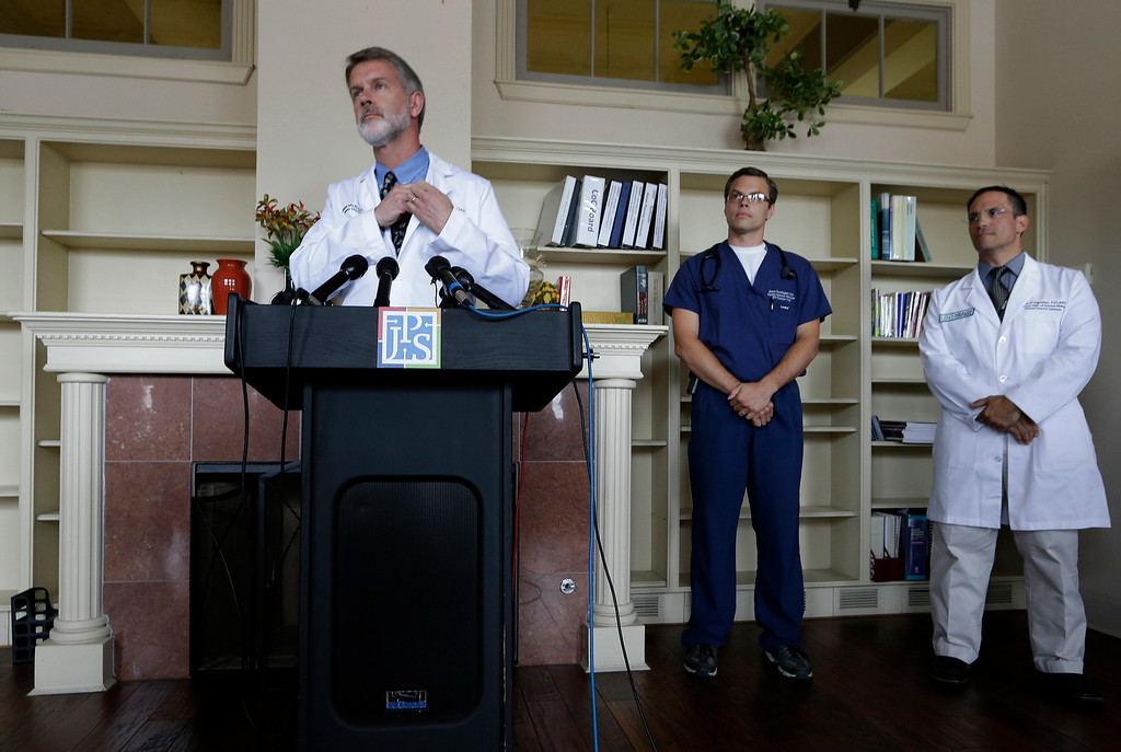 . Dr. David Mcray, left, listens to a question during a news conference with Dr. Jason Brewington, center, and Dr. Darrin D\'Agostino about fellow doctor  Kent Brantly Monday, July 28, 2014, in Fort Worth, Texas. Brantly is one of two American aid workers that have tested positive for the Ebola virus while working to combat an outbreak of the deadly disease at a hospital in Liberia. (AP Photo/LM Otero)
