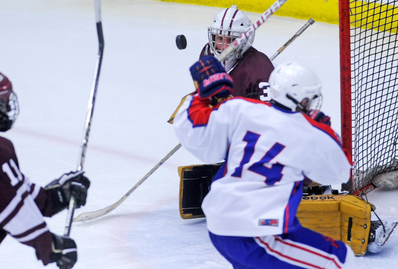 . Cheyenne Mountain goal keeper Grant Payne eyes a shot by Cherry Creek\'s Nick Lardner, right, during the second period of play in 5A High School Hockey action at Family Sports Center in Englewood, CO Saturday December 8, 2012. (Photo by Evan Semon, Special to The Denver Post)