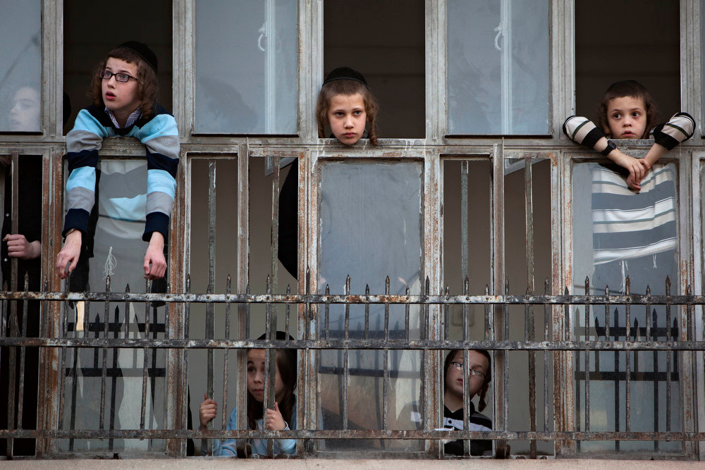Description of . Ultra Orthodox Jewish boys looks out from a window during a preparation of protest calling not to vote in the upcoming election, the Ultra Orthodox Jewish neighborhood of Mea Shearim in Jerusalem, Sunday, Jan. 20, 2013. General elections in Israel are scheduled for Jan. 22, 2013. (AP Photo/Oded Balilty)
