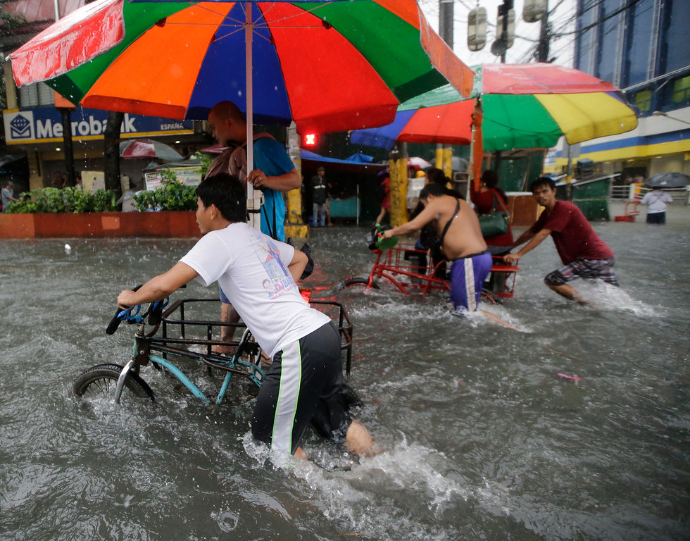 ". Commuters are ferried on a three-wheeled tricycle locally known as ""sidecar\"" after heavy monsoon rains spawned by tropical storm Fung-Wong flooded Manila and most parts of  the metropolis Friday, Sept. 19, 2014 in the Philippines.  (AP Photo/Bullit Marquez)"