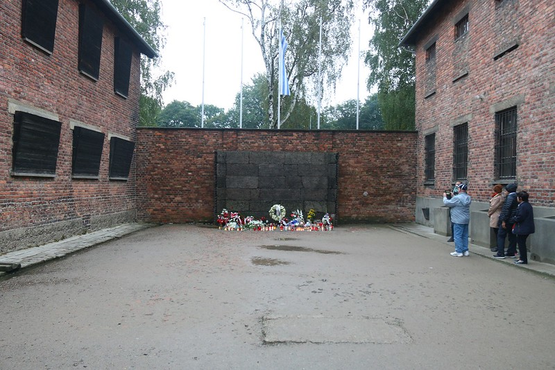 """The """"black wall"""" in the courtyard beside the torture and punishment rooms of  Block 11. After a """"trial"""" that often made a mockery of justice, several thousand convicted prisoners were brought here (over time) and shot in the back of the neck with a single bullet. This is a replica of the original black wall which was dismantled in November 1943 by a newly appointed camp commander replacing Hoess. At that point, level-headed Nazis were beginning to get nervous about post war judgments and punishment."""