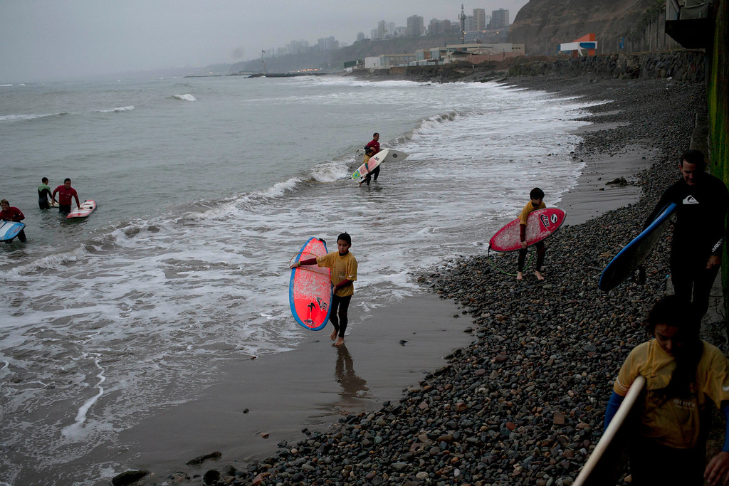 ". In this July 2, 2013 photo, children get out of the sea at the end of a surfing lesson in Lima, Peru. For roughly four months a year, the sun abandons Peru\'s seaside desert capital, suffocating it under a ponderous gray cloudbank and fog that coats the city with nighttime drizzles. The cold Humboldt current that runs north from Antarctica along the coast is the culprit, colliding with the warmer tropical atmosphere to create the blinding mists called ""garua\"" in coastal Chile and Peru. (AP Photo/Rodrigo Abd)"