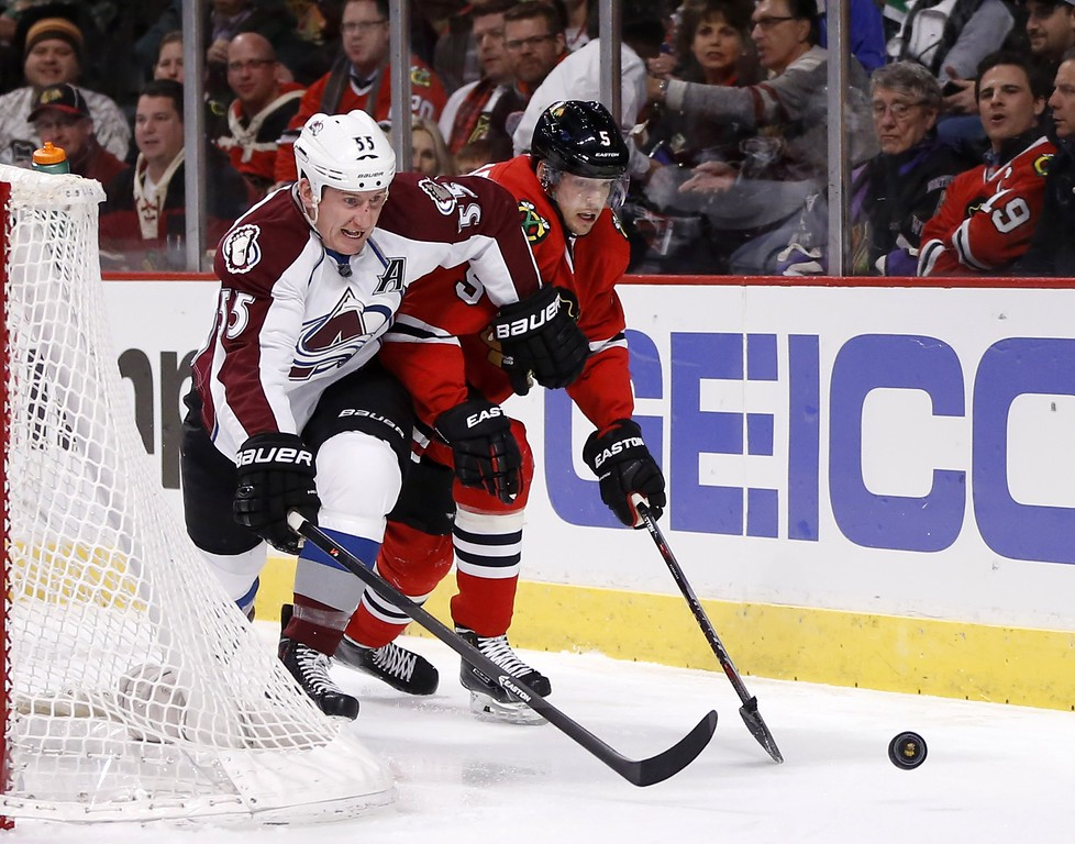 . Colorado Avalanche left wing Cody McLeod (55) and Chicago Blackhawks defenseman David Rundblad (5) battle for the puck behind the Blackhawks\' goal during the first period of an NHL hockey game Tuesday, Jan. 6, 2015, in Chicago. (AP Photo/Charles Rex Arbogast)