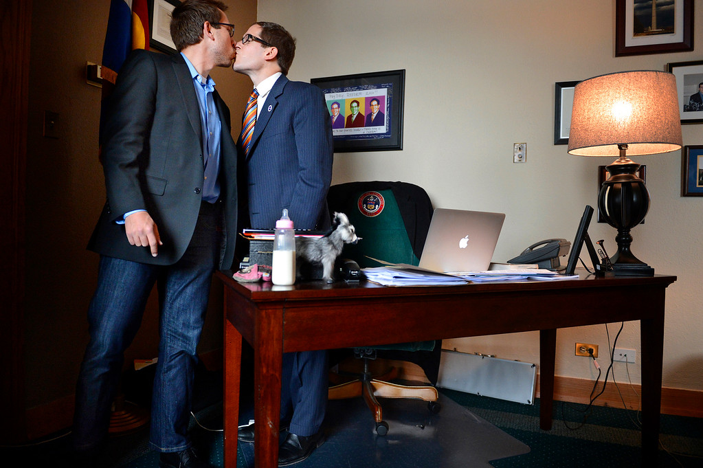 . House Speaker Mark Ferrandino, right, kisses his partner, Greg Wertsch, after the passage of Senate Bill 11 in the Colorado House of Representatives in Denver on March 12, 2013. Ferrandino co-sponsored the bill, which will allow gay couples to form civil unions in Colorado. Wertsch attended the historic vote with the couple\'s foster child.