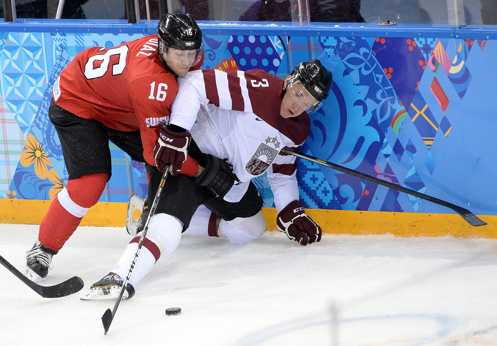 . Switzerland\'s Raphael Diaz (L) vies with Latvia\'s Juris Stals during the Men\'s Ice Hockey Group C match between Latvia and Switzerland at the Sochi Winter Olympics on February 12, 2014 at the Shayba Arena. ANDREJ ISAKOVIC/AFP/Getty Images