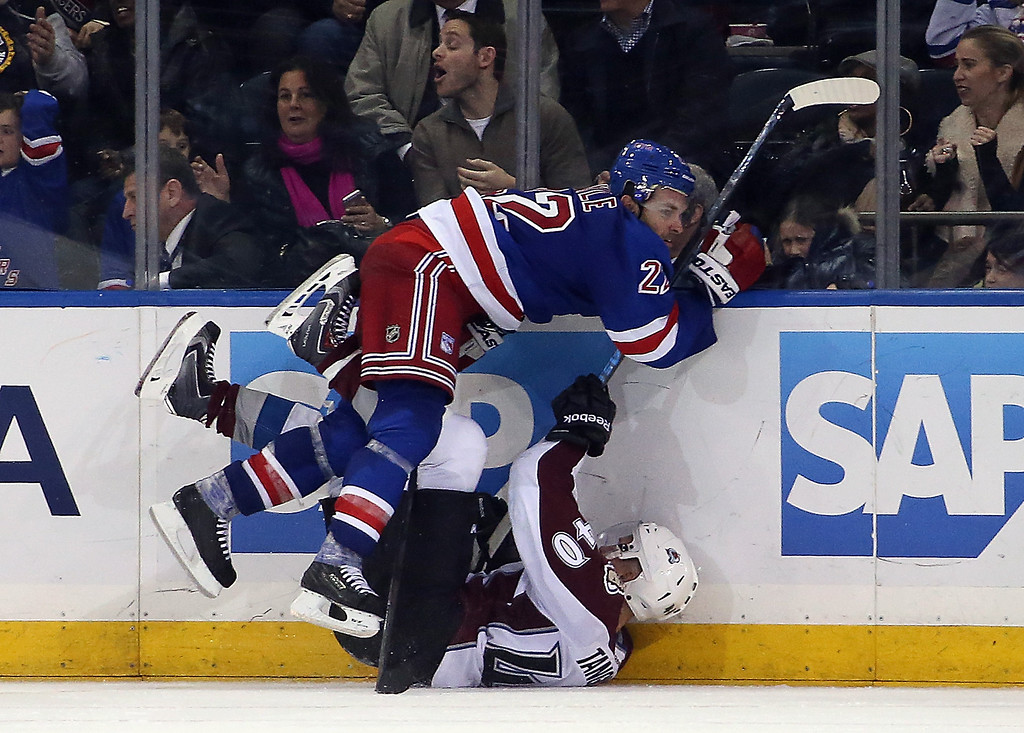 . NEW YORK, NY - NOVEMBER 13: Dan Boyle #22 of the New York Rangers hits Alex Tanguay #40 of the Colorado Avalanche in overtime at Madison Square Garden on November 13, 2014 in New York City. The Avalanche defeated the Rangers 4-3 in the shootout.  (Photo by Bruce Bennett/Getty Images)