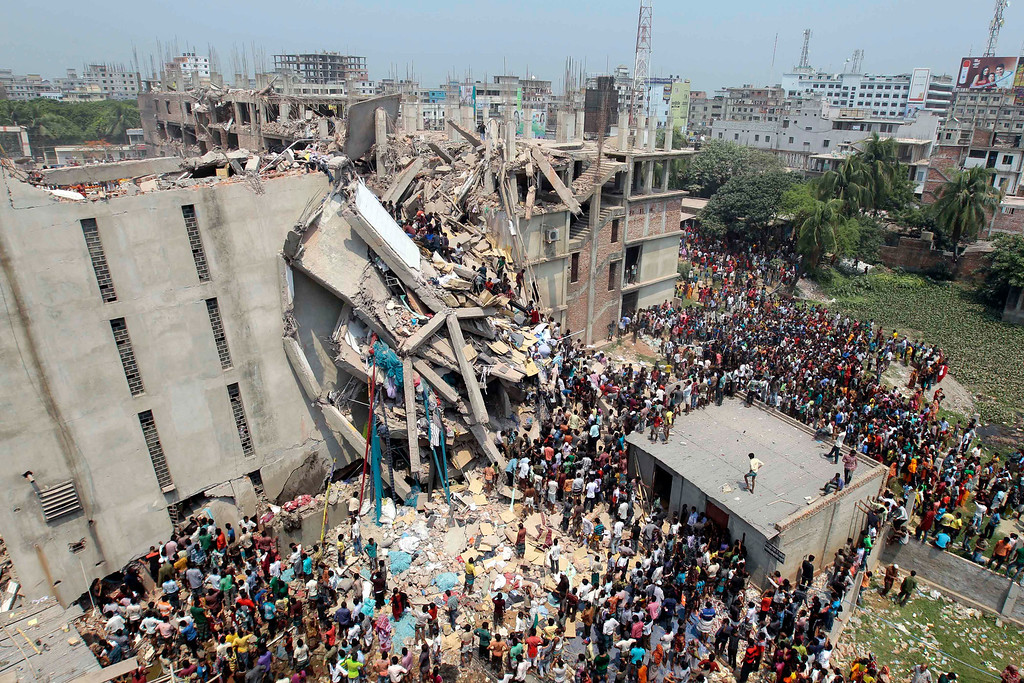 . People and rescuers gather after an eight-story building housing several garment factories collapsed in Savar, near Dhaka, Bangladesh, Wednesday, April 24, 2013. Dozens were killed and many more are feared trapped in the rubble. (AP Photo/ A.M. Ahad)