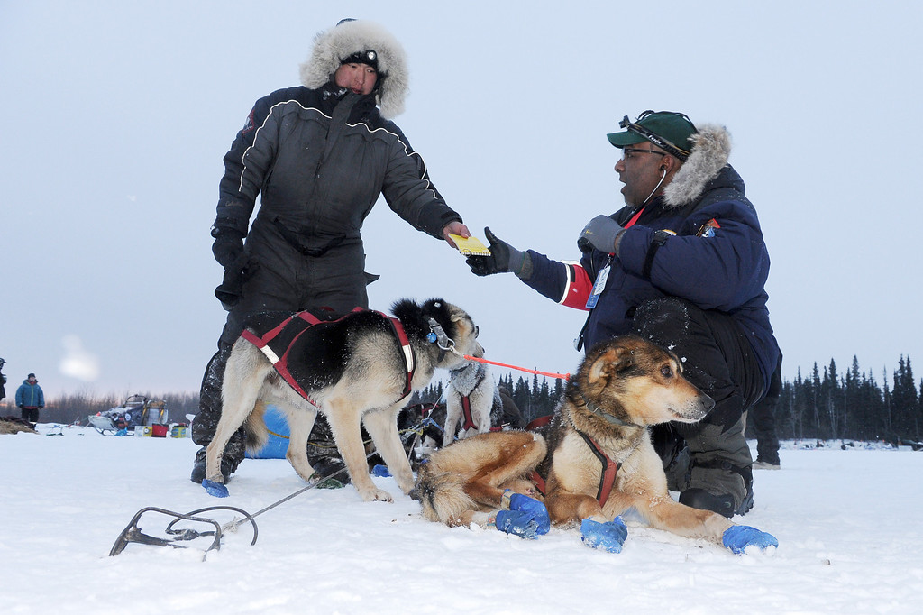. Musher Mike Williams Jr. hands his vet book to veterinarian Bruce Nwadike at the Nikolai checkpoint during the 2014 Iditarod Trail Sled Dog Race on Tuesday, March 4, 2014.   (AP Photo/The Anchorage Daily News, Bill Hallinen)