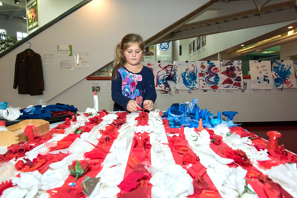 11/12/18 Wesley Bunnell | Staff Alexsa Buzak, age 5, helps decorate an american flag in art class at Imagine Nation on Monday afternoon. The flag, which has been worked since July 4, will eventually be presented to the Newington VA as a gift.