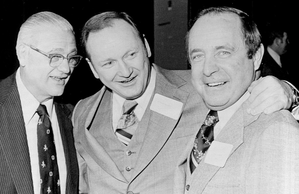 . Former Ohio State football coach Woody Hayes, left, jokes with University of Michigan coach Bo Schembechler, center, and Ohio State coach Earle Bruce, as Hayes was saluted at a dinner held in his honor in Cleveland, Ohio, March 2, 1979. (AP Photo/Doug Martin)