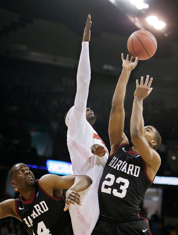. Harvard\'s Wesley Saunders (23) shoots as Cincinnati\'s Justin Jackson defends during the first half of a second-round game of the NCAA college basketball tournament in Spokane, Wash., Thursday, March 20, 2014. (AP Photo/Young Kwak)
