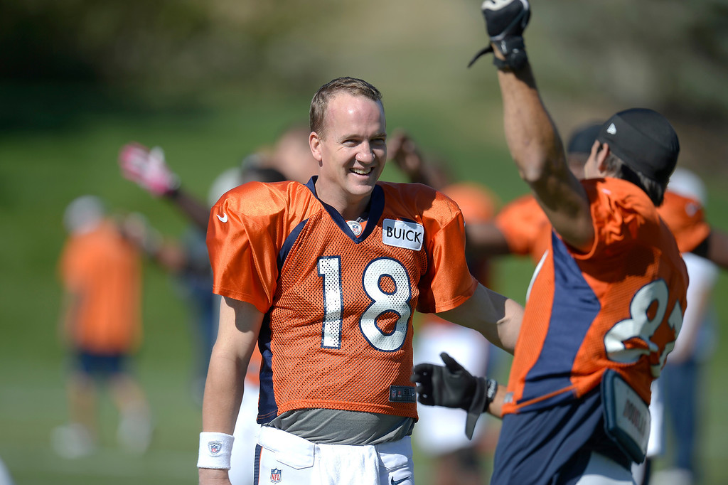 . Denver Broncos quarterback Peyton Manning (18) smiles as he talks with Denver Broncos wide receiver Eric Decker (87) before practice. (Photo by John Leyba/The Denver Post)