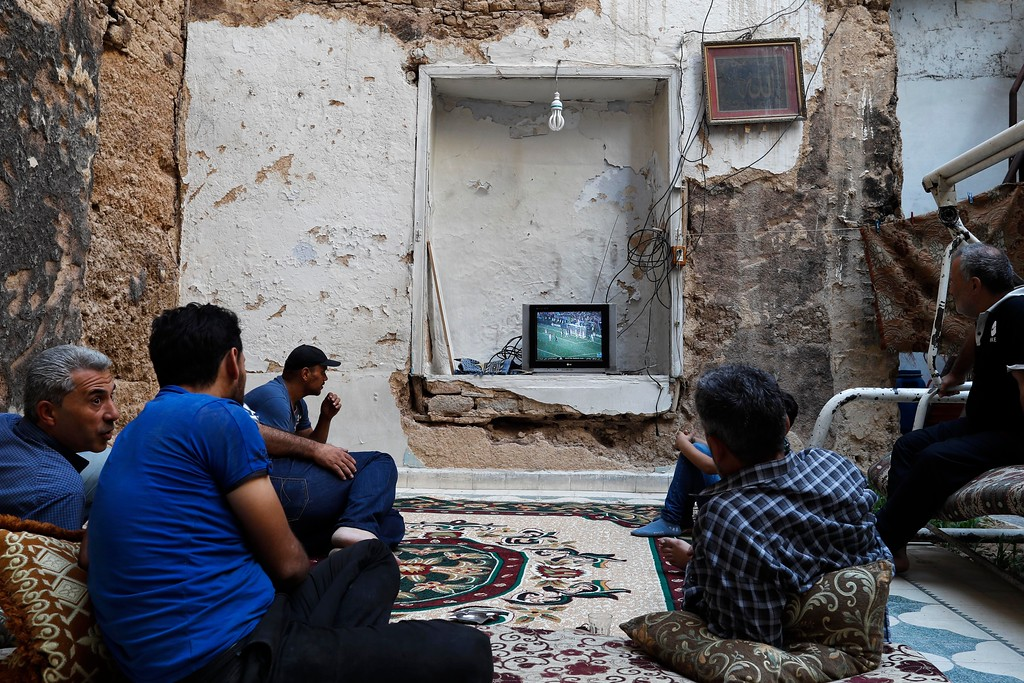 . Syrians watch the World Cup soccer final match between France and Croatia at their home, that was partially destroyed by the war leaving two of its rooms without a ceiling, in the town of Ain Terma, in the Eastern Ghouta suburb of Damascus, Syria, Sunday, July 15, 2018. (AP Photo/Hassan Ammar)