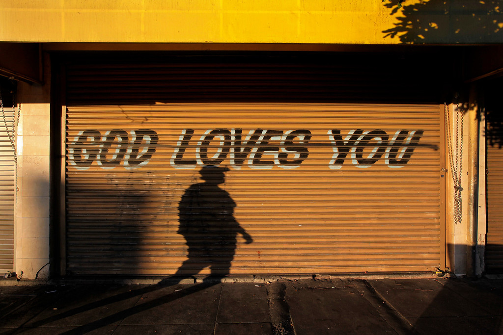 ". A woman casts a shadow on the shutters of a closed store with a ""God Loves You\"" message written on it in the Skid Row area of Los Angeles on Monday, Sept. 16, 2013. (AP Photo/Jae C. Hong)"