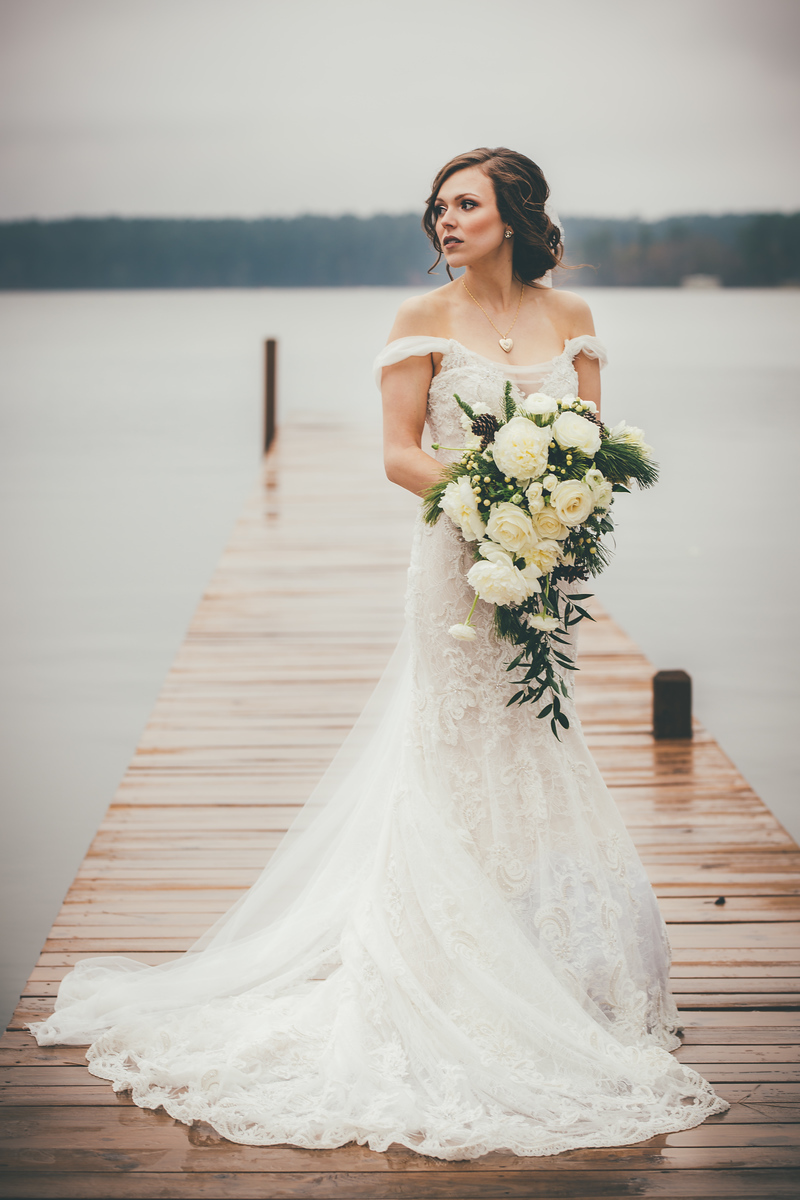 A bride standing on a doc of Lake Tyler before her wedding ceremony