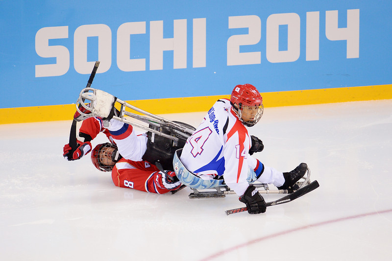 . Dmitrii Lisov of Russia is challenged by Seung-Hwan Jung of Korea during the Ice Sledge Hockey Preliminary Round Group A match between the Russia and Korea at Shayba Arena on March 8, 2014 in Sochi, Russia.  (Photo by Dennis Grombkowski/Getty Images)