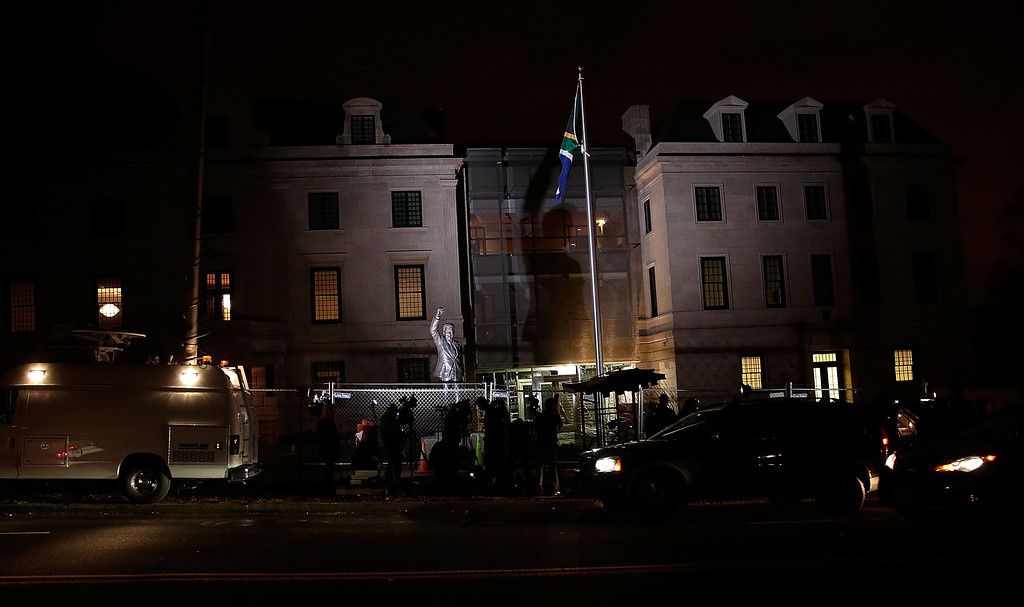 . WASHINGTON, DC - DECEMBER 06:  News crews gather around a statue of former South African President Nelson Mandela outside the South African Embassy December 5, 2013 in Washington, DC. Incumbent South African President Jacob Zuma announced earlier that Mandela has died at the age of 95.  (Photo by Win McNamee/Getty Images)