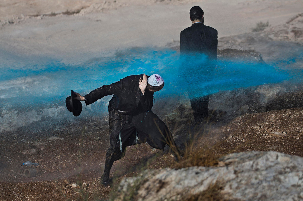 . An ultra-Orthodox Jewish protester is sprayed with a colored liquid from a water canon by Israeli police, not pictured, on a construction site in Ramat Beit Shemesh, Israel, Wednesday, Aug. 14, 2013. A group of ultra-Orthodox Jews claimed ancient graves will be desecrated during the construction of a new housing project. (AP Photo/Bernat Armangue)