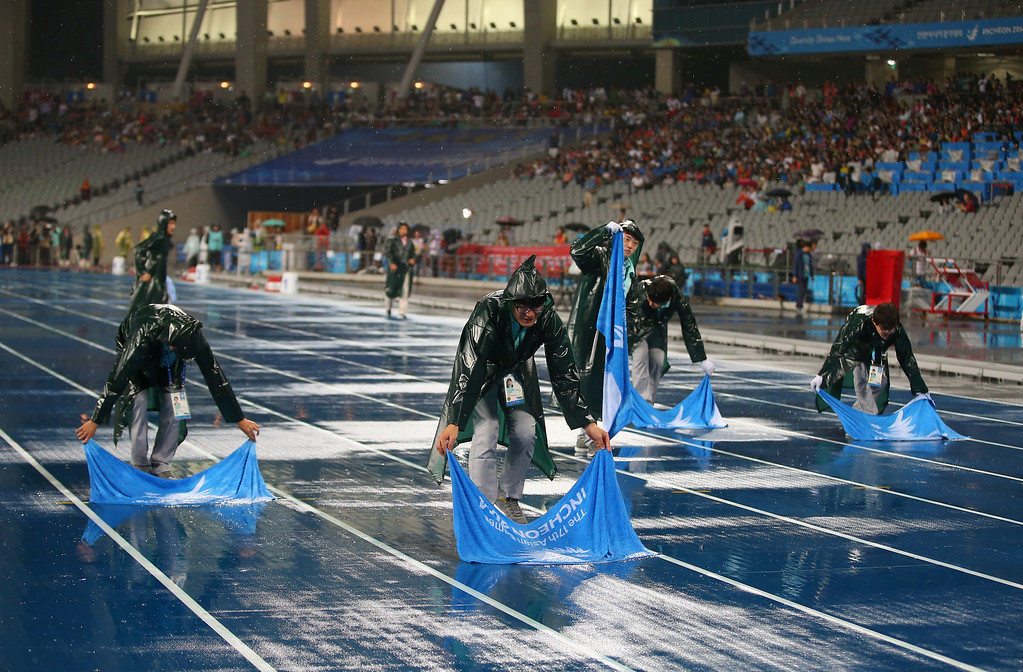 . =Volunteers wipe the track with towels prior to the Women\'s 100m Final during day nine of the 2014 Asian Games at Incheon Asiad Main Stadium on September 28, 2014 in Incheon, South Korea.  (Photo by Brendon Thorne/Getty Images)