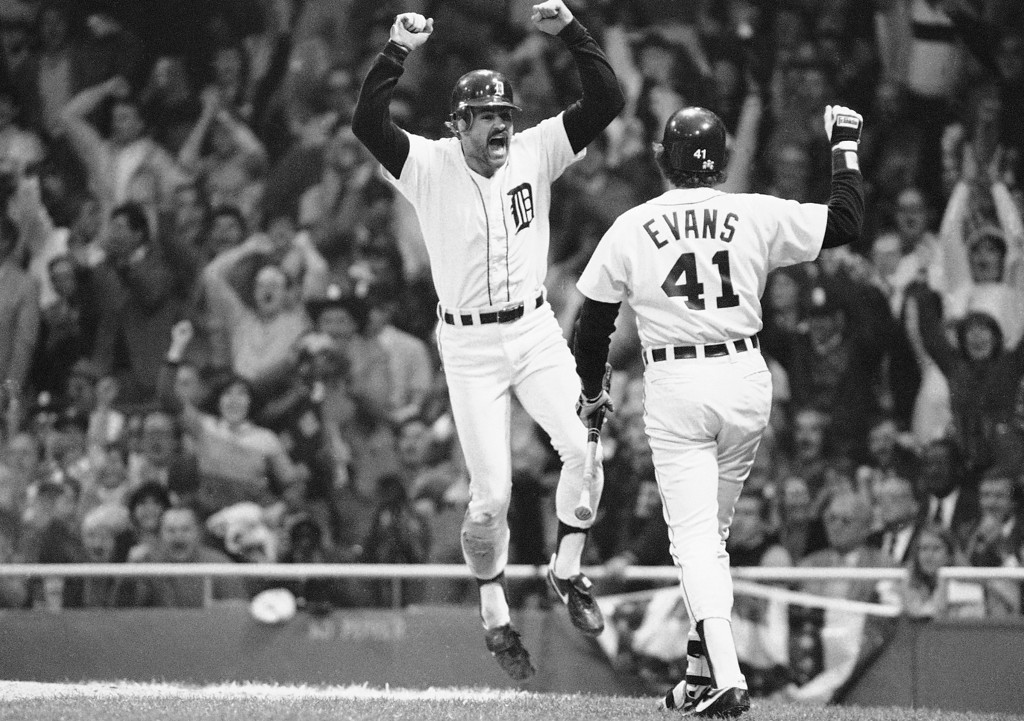 . Kirk Gibson of Detroit, left, jumps with joy after scoring from third on Rusty Kuntz sacrifice fly in the fifth inning in World Series action at Tiger Stadium, Sunday, Oct. 14, 1984, Detroit, Mich. Darrell Evans is the on-deck batter. (AP Photo/Rusty Kennedy)