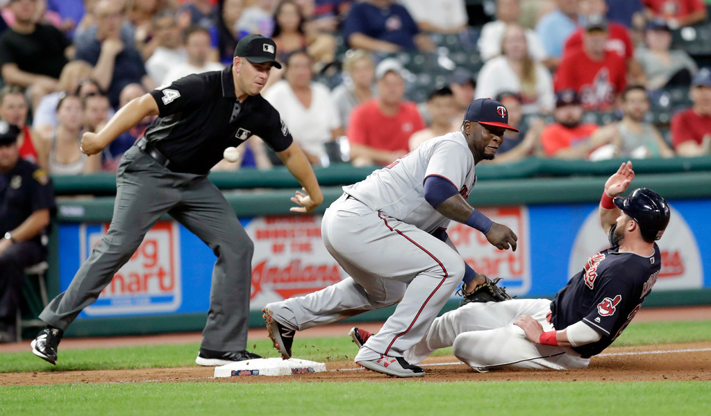 . Cleveland Indians\' Jason Kipnis slides safely into third base as Minnesota Twins\' Miguel Sano lets the ball get by in the sixth inning of a baseball game, Tuesday, Aug. 28, 2018, in Cleveland. Umpire John Libka watches. (AP Photo/Tony Dejak)