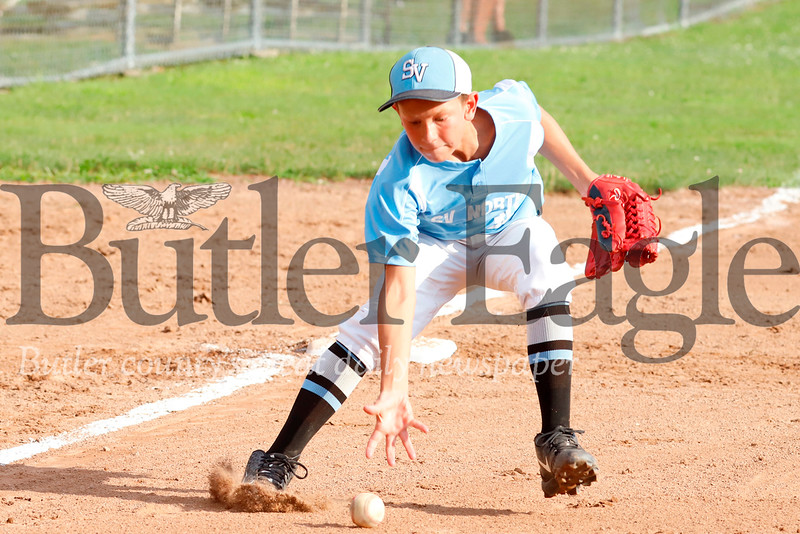 Seneca U10 all star tournament team third baseman Jaxson Householder bare hands a grounder  to try to catch a runner at first during tournament play against Shaler Thursday evening in Zelienople. Seb Foltz/Butler Eagle