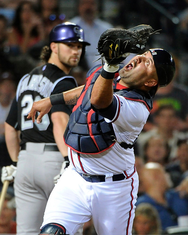 . Atlanta Braves catcher Gerald Laird, right, catches a pop-out by Colorado Rockies\' Charlie Culberson (23) during the sixth inning of a baseball game Friday, May 23, 2014, in Atlanta. (AP Photo/David Tulis)