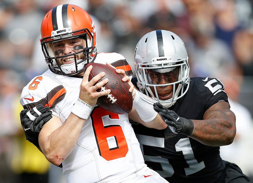 . Cleveland Browns quarterback Baker Mayfield (6) tries to escape the grasp of Oakland Raiders defensive end Bruce Irvin (51) during the first half of an NFL football game in Oakland, Calif., Sunday, Sept. 30, 2018. (AP Photo/D. Ross Cameron)