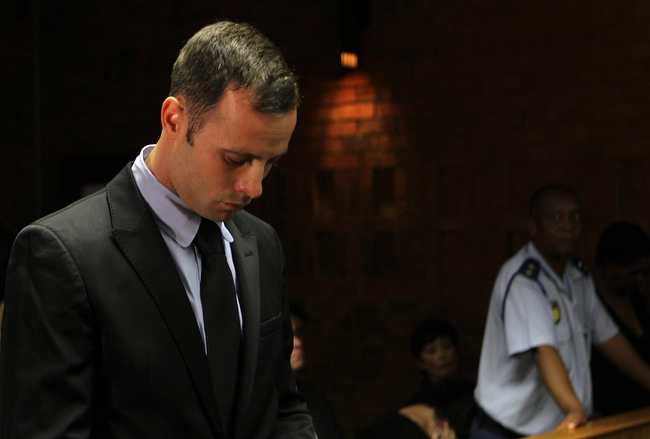 ". Olympic athlete Oscar Pistorius stands inside the court as a police officer looks on during his bail hearing at the magistrate court in Pretoria, South Africa, Wednesday, Feb. 20, 2013. A South African judge says defense lawyers will need to offer ""exceptional\"" reasons to convince him to grant bail for Oscar Pistorius, when a hearing resumes Wednesday. (AP Photo/Themba Hadebe)"
