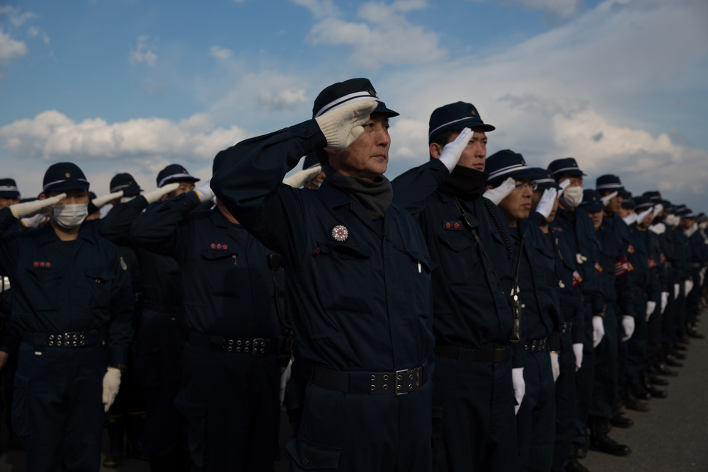 . Police officers salute during 3rd anniversary ceremony on March 10, 2014 in Fukushima, Japan. On March 11 Japan commemorates the third anniversary of the magnitude 9.0 earthquake and tsunami that claimed more than 18,000 lives, and subsequent nuclear disaster at the Fukushima Daiichi Nuclear Power Plant.  (Photo by Ken Ishii/Getty Images)