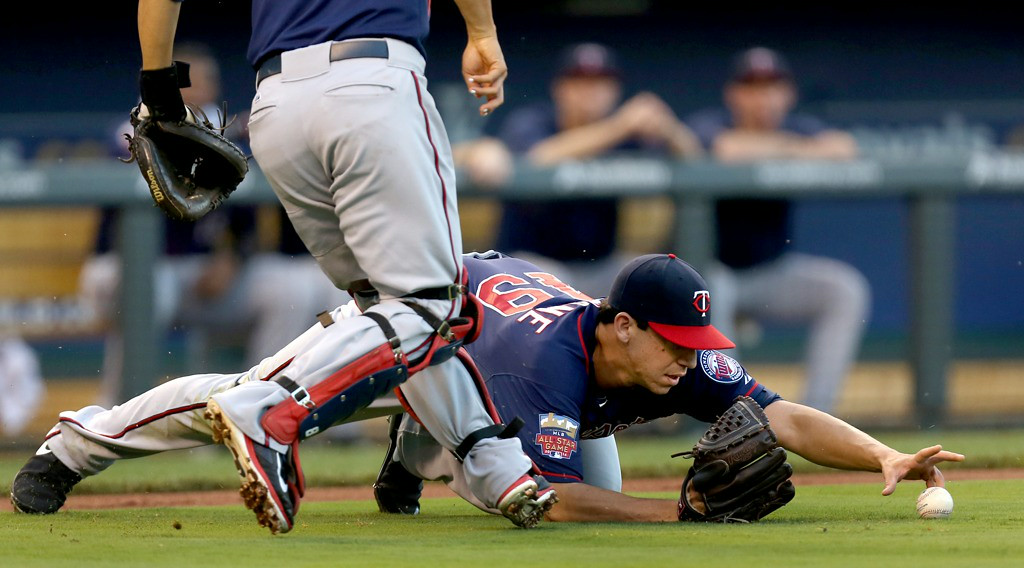 . Twins pitcher Tommy Milone and catcher Kurt Suzuki chase down a bunted ball by Royals\' Alcides Escobar in the first inning. (Photo by Ed Zurga/Getty Images)