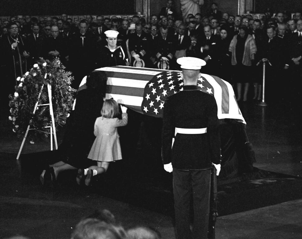 . Mrs. John F. Kennedy kisses the casket of her husband in the rotunda of the U.S. Capitol, November 24, 1963.  Daughter Caroline kneels alongside.  (AP Photo/stf)