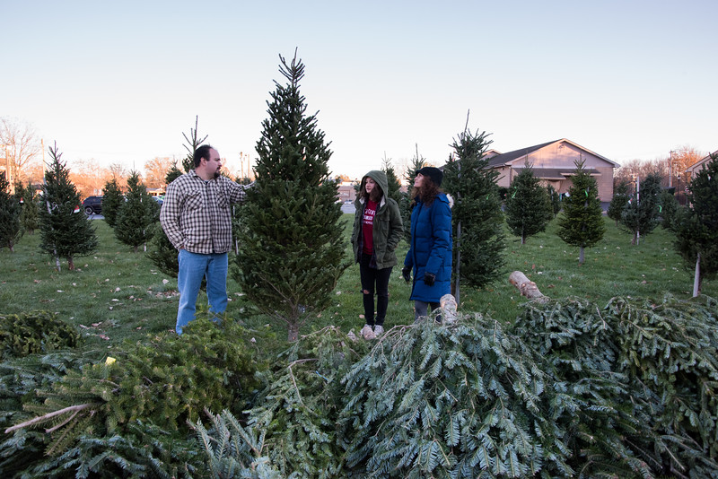 11/24/17  Wesley Bunnell | Staff  Dennis DeCesare holds up a possible Christmas tree at the Kiwanis of Berlin tree sale at Massirio Drive on Friday afternoon as he discusses it with Nicole Vasil and Brooke Barbero.