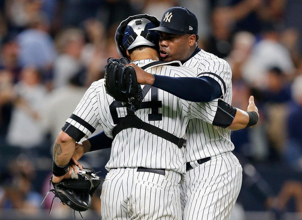 . New York Yankees pitcher Aroldis Chapman, right, hugs catcher Gary Sanchez (24) after the Yankees beat the Cleveland Indians 1-0 in Game 3 of baseball\'s American League Division Series, Sunday, Oct. 8, 2017, in New York. (AP Photo/Kathy Willens)