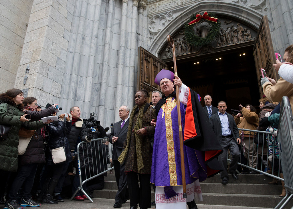 . From center left, NYPD Commissioner Bill Bratton, New York City first lady Chirlane McCray, New York City Mayor Bill de Blasio, and Cardinal Timothy Dolan exit St. Patrick\'s Cathedral following a Mass, Sunday, Dec. 21, 2014, in New York. The previous day, an armed man walked up to two New York Police officers sitting inside a patrol car and opened fire, killing both before running into a nearby subway station and committing suicide, police said. (AP Photo/John Minchillo)