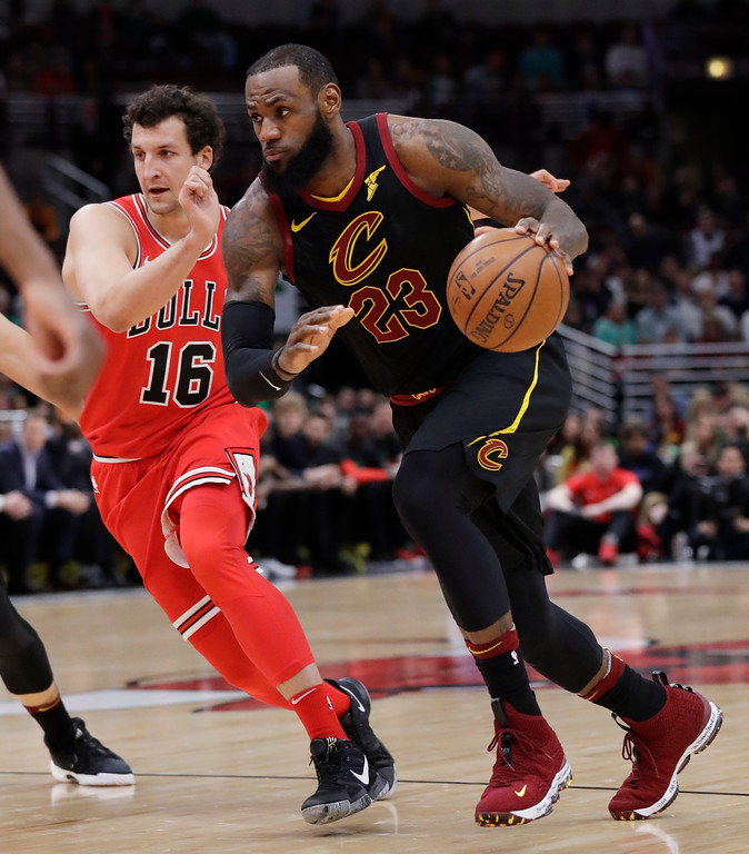 . Cleveland Cavaliers forward LeBron James, right, drives to the basket against Chicago Bulls forward Paul Zipser during the first half of an NBA basketball game Saturday, March 17, 2018, in Chicago. (AP Photo/Nam Y. Huh)