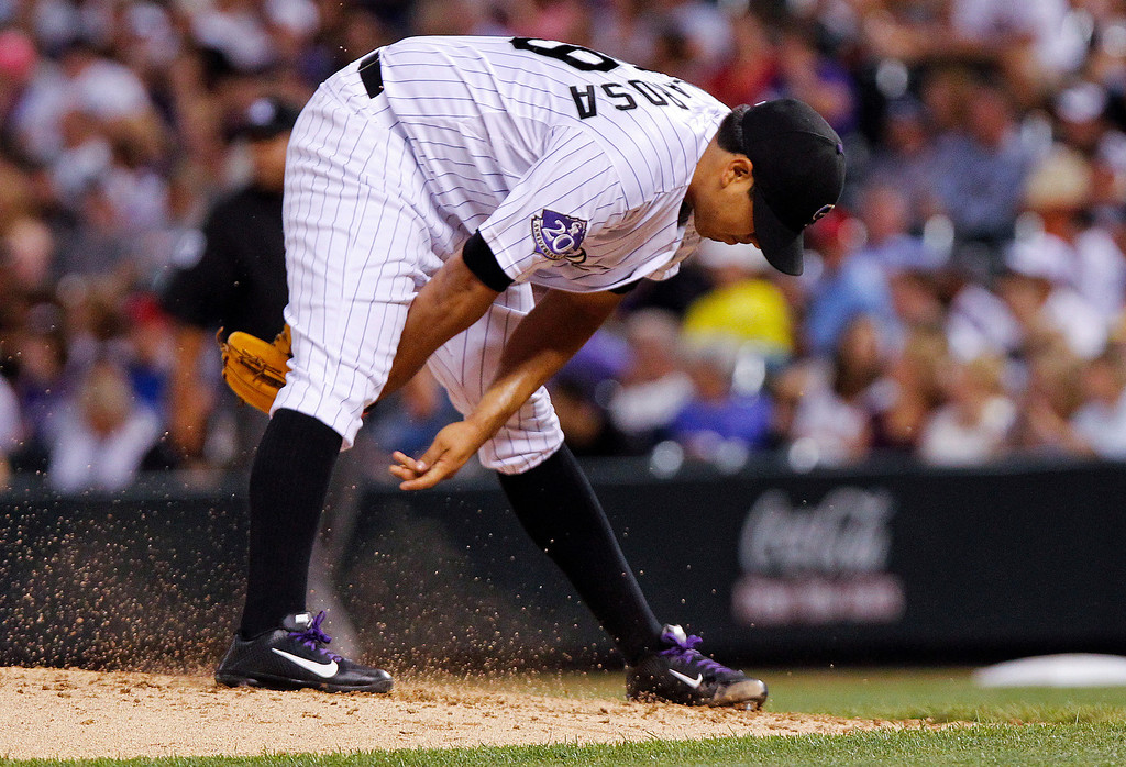 . Colorado Rockies starting pitcher Jorge De La Rosa brushes dirt between his legs after giving up an RBI-single by Cincinnati Reds\' Ryan Hanigan during the fourth inning of a baseball game on Friday, Aug. 30, 2013, in Denver. (AP Photo/Barry Gutierrez)