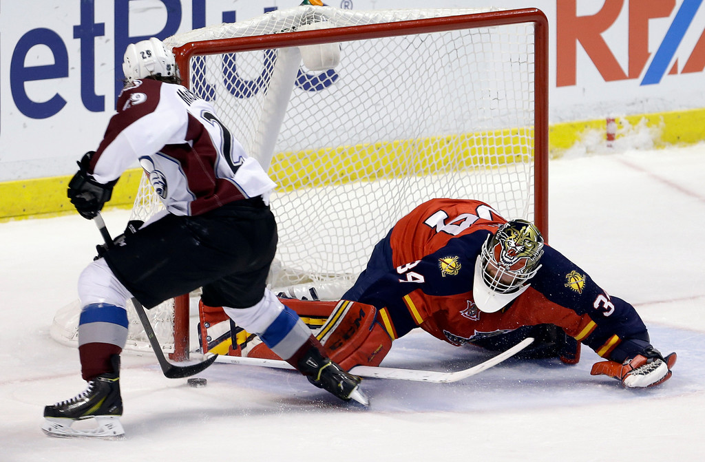 . Florida Panthers goalie Tim Thomas (34) blocks a shot by Colorado Avalanche center Nathan MacKinnon (29) during the second period of an NHL hockey game in Sunrise, Fla., Friday, Jan. 24, 2014. (AP Photo/Alan Diaz)