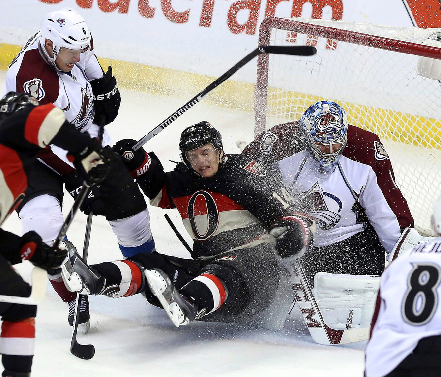 . Ottawa Senators\' Colin Greening (14) is checked by Colorado Avalanche\'s Erik Johnson (6) into Avalanche goaltender Semyon Varlamov (1) during second-period NHL hockey game action in Ottawa, Ontario, Sunday March 16, 2014. (AP Photo/The Canadian Press, Fred Chartrand)